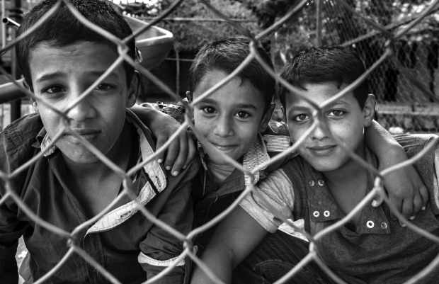 grayscale photography of three boys beside steel fence