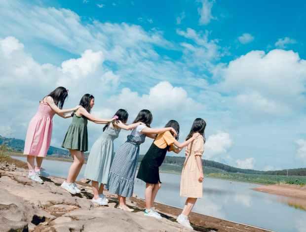 six women standing near body of water